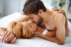 ベッドで重なるようにキスするカップル