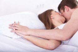 ベッドで手を合わせるカップル